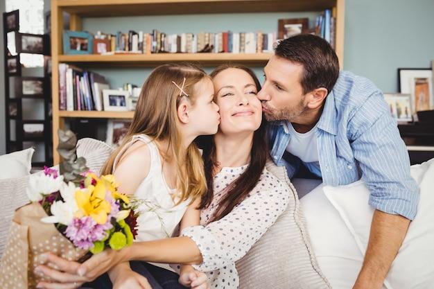 Pai e filha beijando a mãe