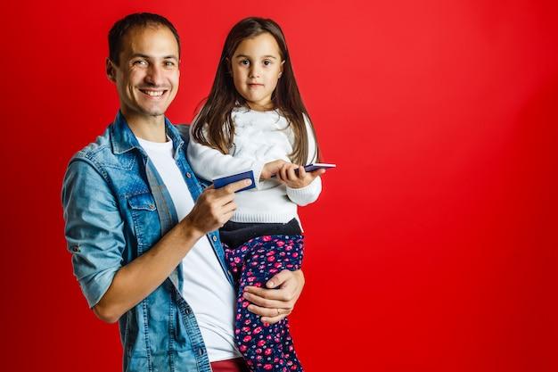 Pai e filha bonita com passaporte em fundo vermelho