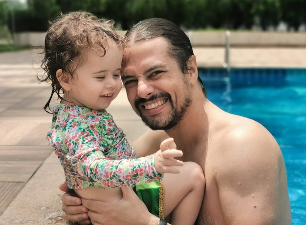 Pai e filha brasileiros se divertindo na piscina.