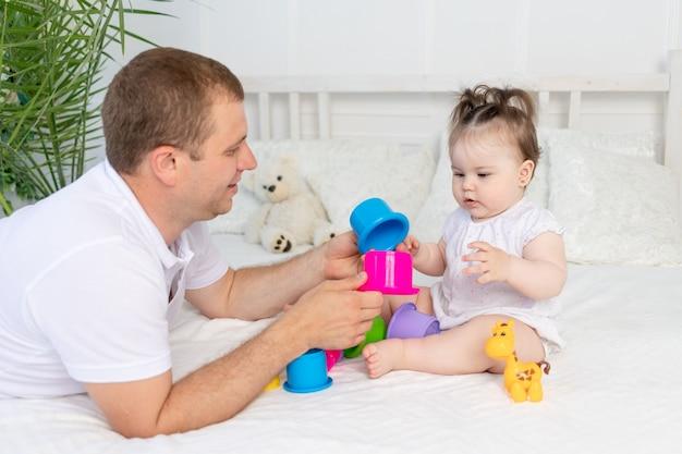Pai e filha brincam com brinquedos coloridos na cama em casa em um quarto bem iluminado