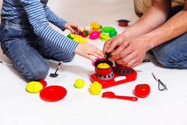 Pai e filha brincam com frutas e vegetais fatiados de plástico com velcro, cozinha comida em um fogão de brinquedo em uma tigela. cozinha infantil, uma menina aprende a cozinhar. fundo branco, close-up. dia dos pais