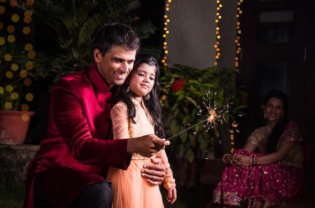 Pai e filha brincando com biscoitos de fogo ou fulzadi na noite de diwali