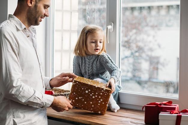 Pai e filha brincando com caixas de presente perto da janela