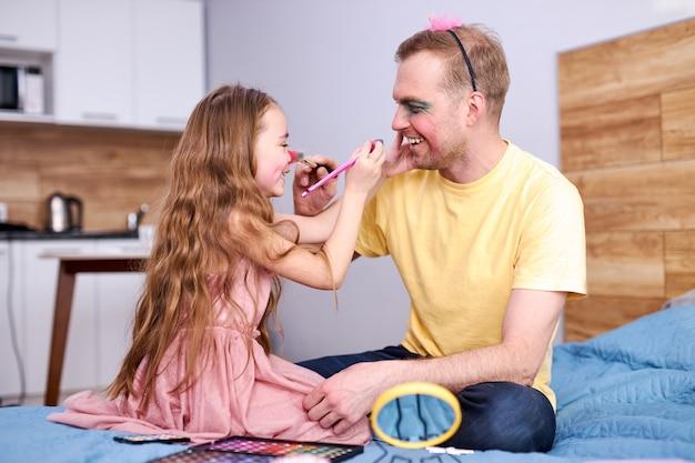 Pai e filha brincando em casa com pincel de maquiagem fazendo maquiagem no rosto