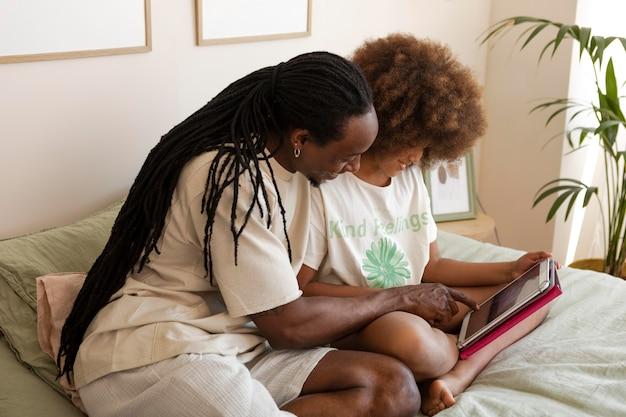 Pai e filha brincando juntos em um tablet
