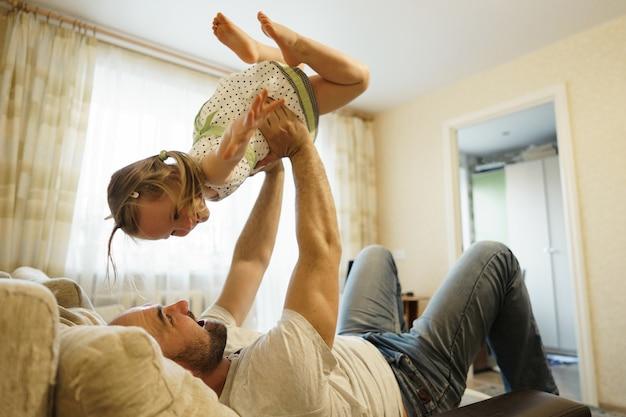 Pai e filha brincando no sofá no avião. conceito de família