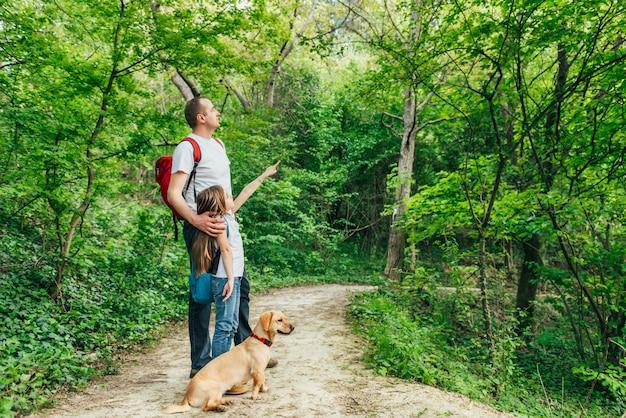 Pai e filha caminhando pela floresta com cachorro