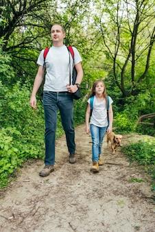 Pai e filha caminhando pela floresta