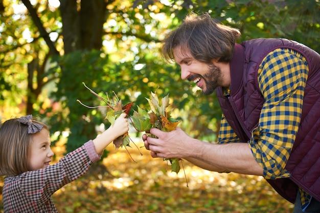 Pai e filha colhendo folhas no outono