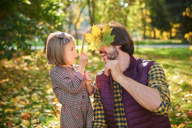 Pai e filha colhendo folhas outonais