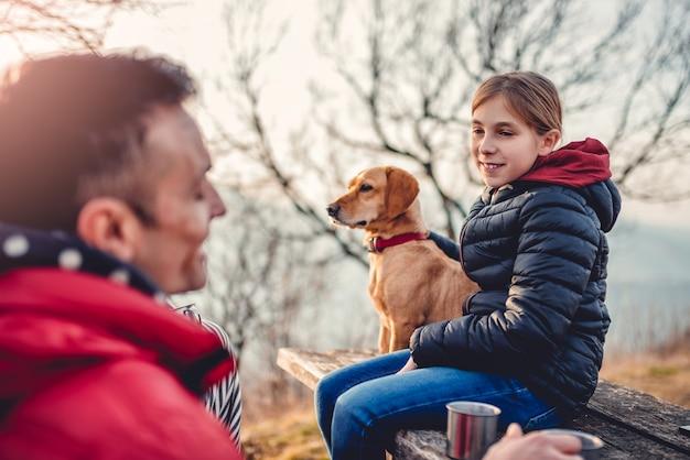 Pai e filha com cachorro sentado em uma mesa de piquenique e conversando
