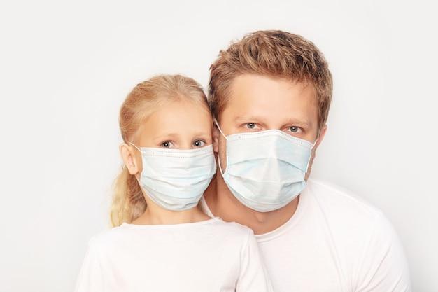 Pai e filha com máscaras médicas juntos em um fundo isolado.