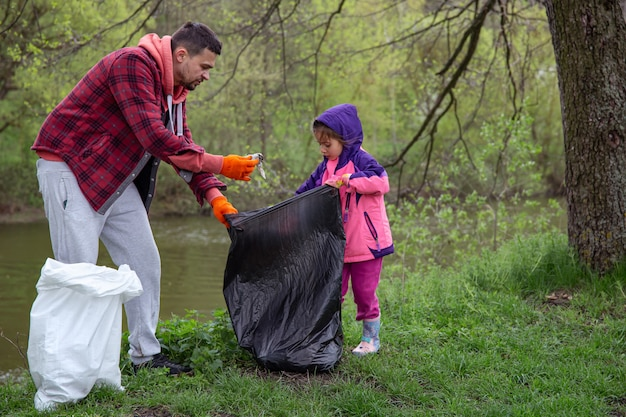 Pai e filha, com sacos de lixo, limpam o meio ambiente do lixo.
