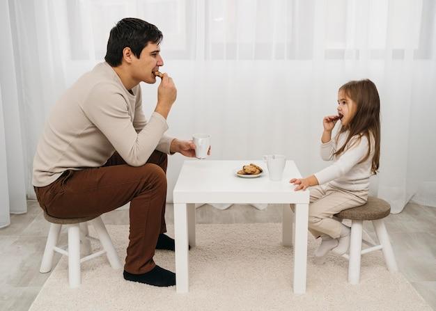 Pai e filha comendo juntos em casa