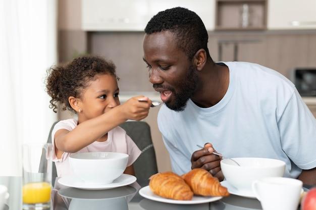 Pai e filha comendo juntos Foto gratuita
