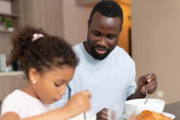 Pai e filha comendo juntos