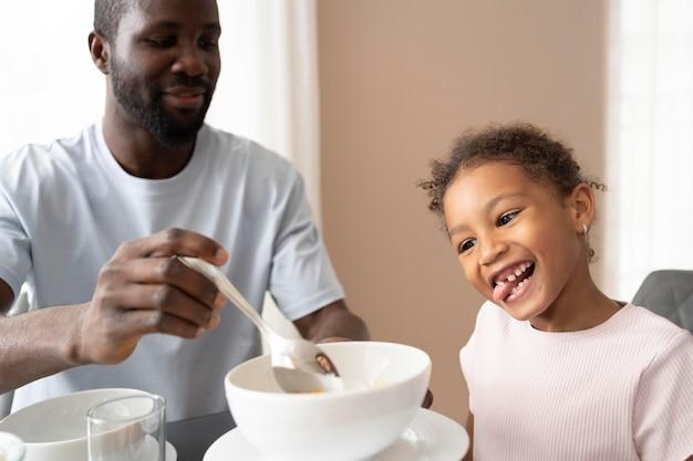 Pai e filha comendo na cozinha