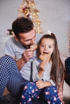 Pai e filha comendo pão de gengibre no natal
