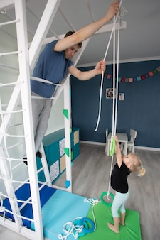 Pai e filha construindo complexo esportivo. reforma da casa e dia dos pais. interior do quarto infantil