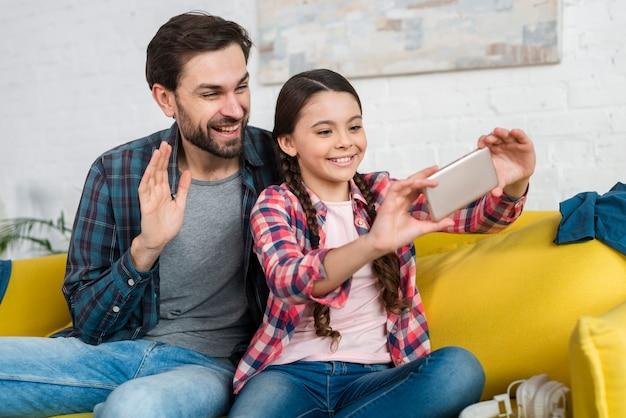 Pai e filha conversando com alguém em uma vídeo chamada