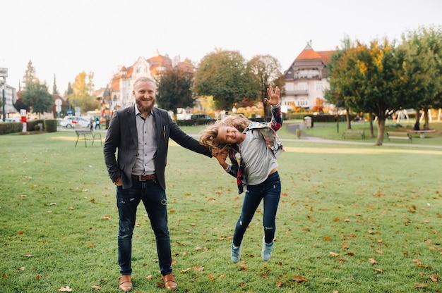 Pai e filha correndo na grama na cidade velha da áustria