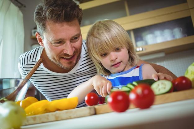 Pai e filha cortando legumes na cozinha