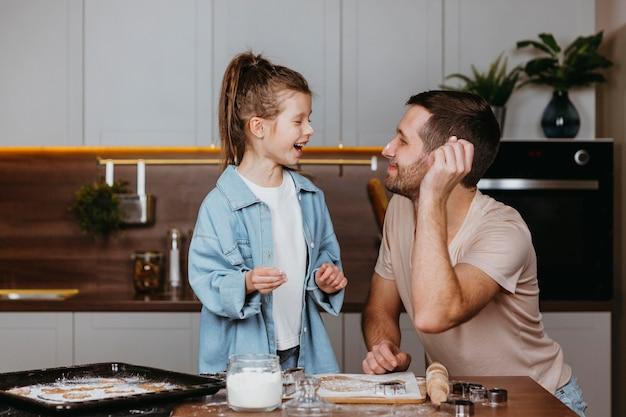 Pai e filha cozinhando juntos na cozinha de casa