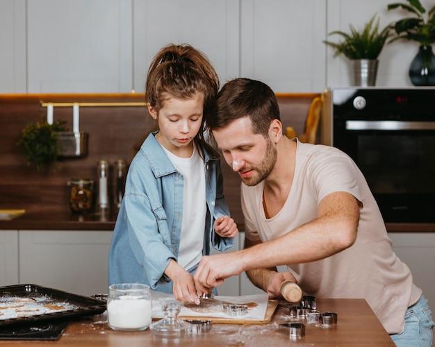 Pai e filha cozinhando juntos na cozinha