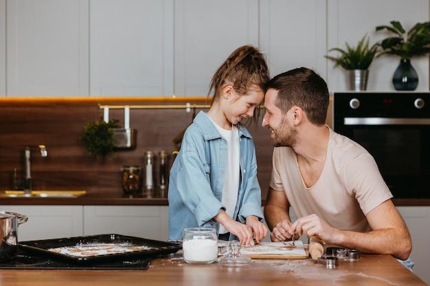 Pai e filha cozinhando na cozinha de casa juntos
