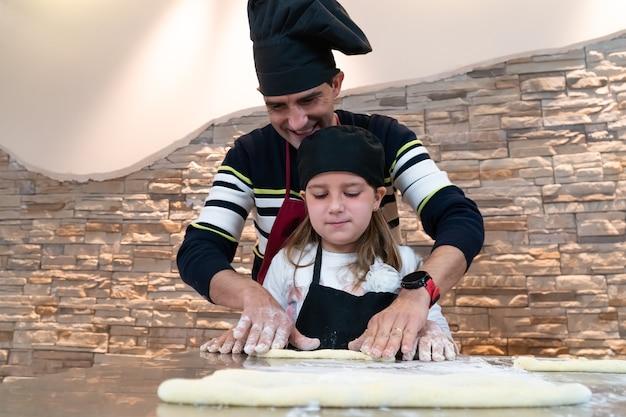 Pai e filha cozinhando uma massa juntos, fantasiados de chef