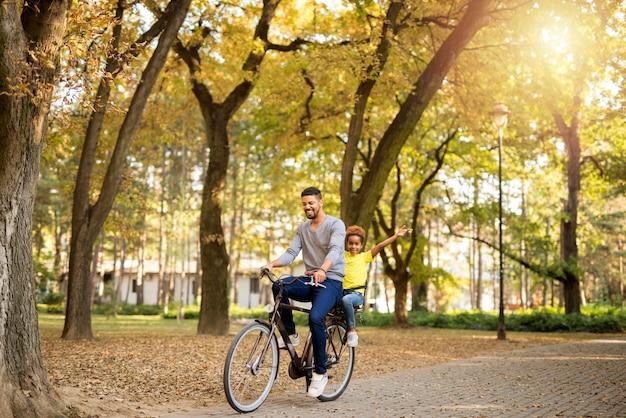 Pai e filha curtindo um passeio de bicicleta na natureza