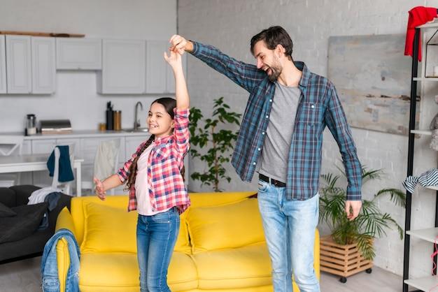 Pai e filha dançando na sala de estar