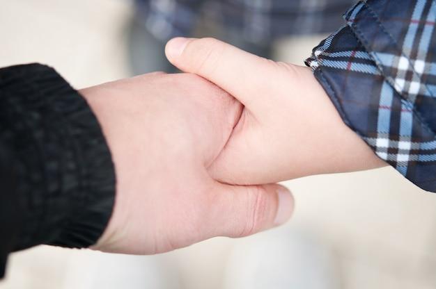 Pai e filha de mãos dadas.