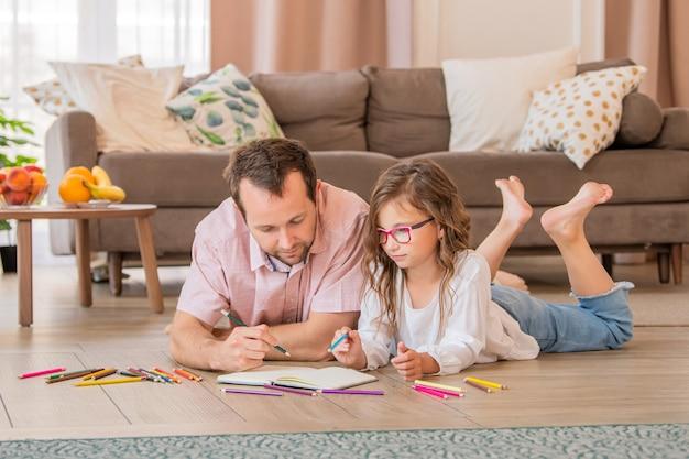 Pai e filha de óculos estão desenhando juntos enquanto estavam deitados no chão do quarto do apartamento.