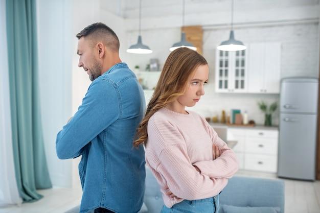 Pai e filha de pé, costas com costas, os braços cruzados, cada um olhando tristemente à sua frente.