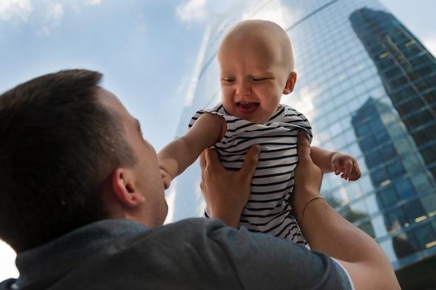Pai e filha de um ano contra o céu e arranha-céus. viajar com crianças, o desenvolvimento da inteligência emocional.