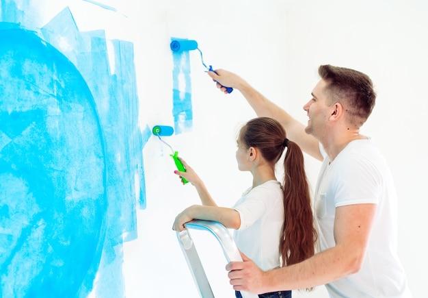 Pai e filha dele pintando uma parede na nova casa.