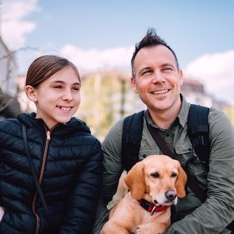 Pai e filha descansando em uma rua da cidade com seu cachorro