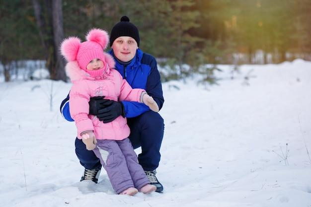 Pai e filha descansando na floresta de inverno