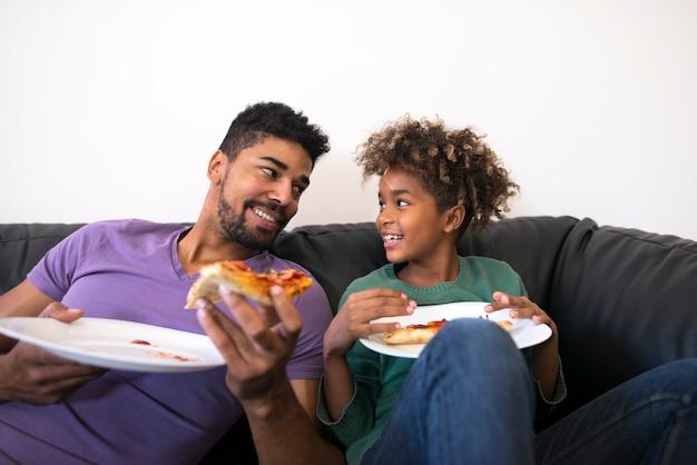 Pai e filha desfrutando de pizza no confortável sofá da sala.
