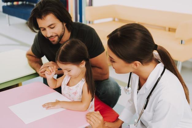 Pai e filha draw play no consultório médico.
