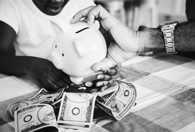 Pai e filha economizando dinheiro em um cofrinho