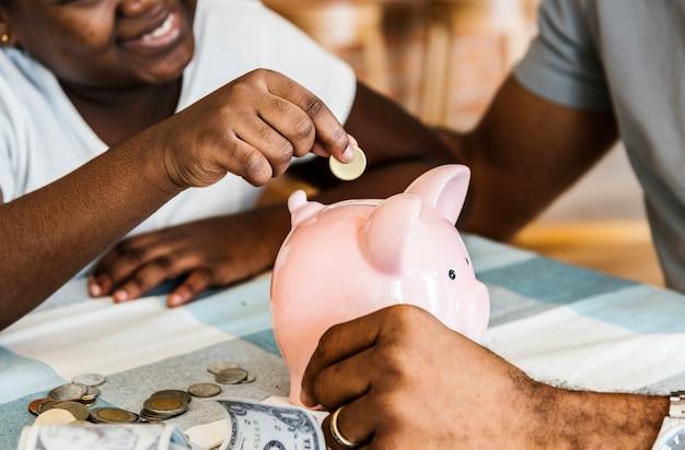 Pai e filha economizando dinheiro para cofrinho