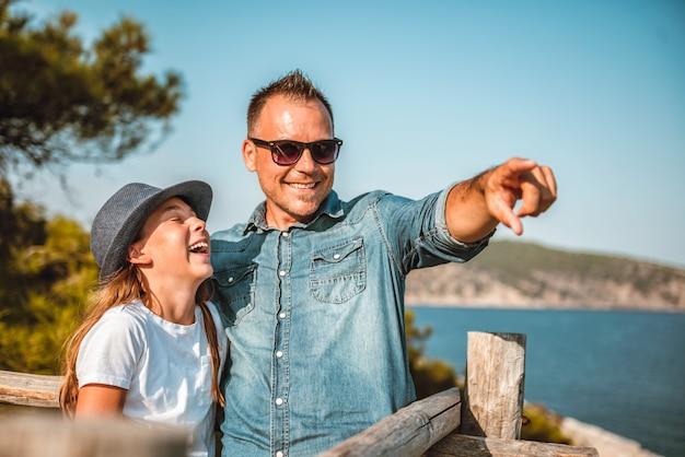 Pai e filha em pé à beira-mar e olhando para o horizonte