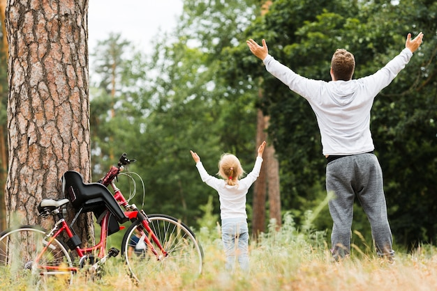 Pai e filha em pé com as mãos no ar