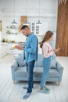 Pai e filha em pé, costas com costas, no meio da sala, perto do sofá, cada um olhando para seu smartphone.