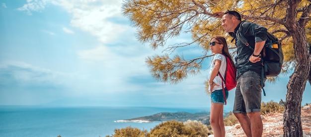 Pai e filha em pé em um penhasco à beira-mar