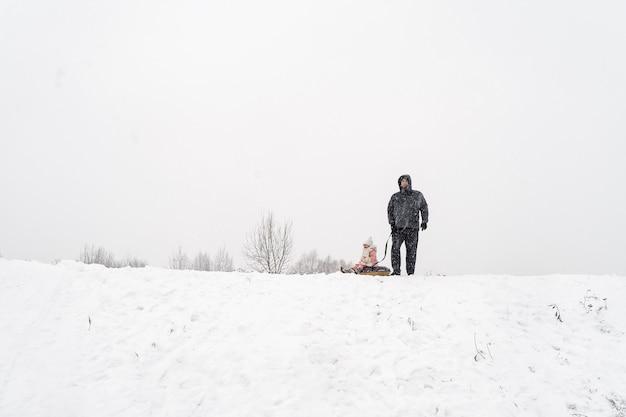 Pai e filha em um escorregador de neve com tubos em uma nevasca