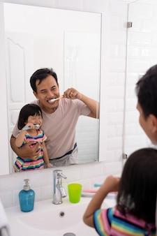 Pai e filha escovando os dentes juntos