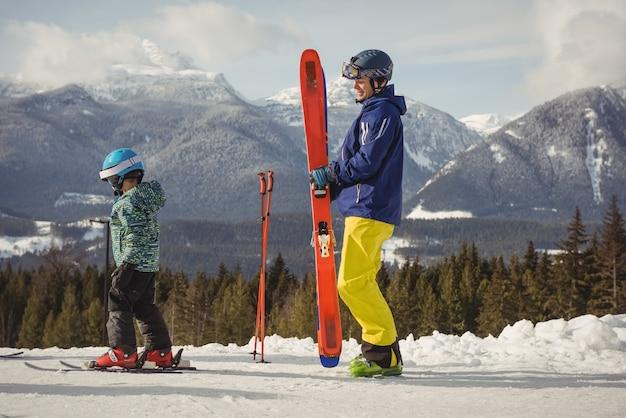Pai e filha esquiando nos alpes nevados